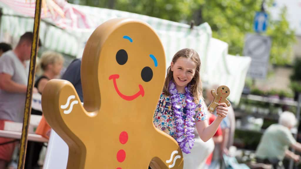 A young girl with the Ormskirk Gingerbread statue