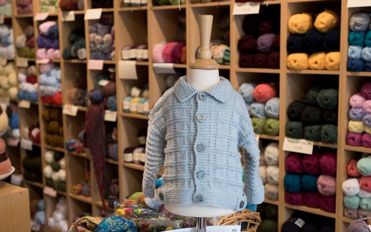 Knitted cardigan and display of wool